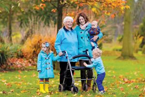Happy senior lady with a walker and children. Grandmother and kids enjoying a walk in the park. Child supporting disabled grandparent. Family visit. Generations love and relationship.
